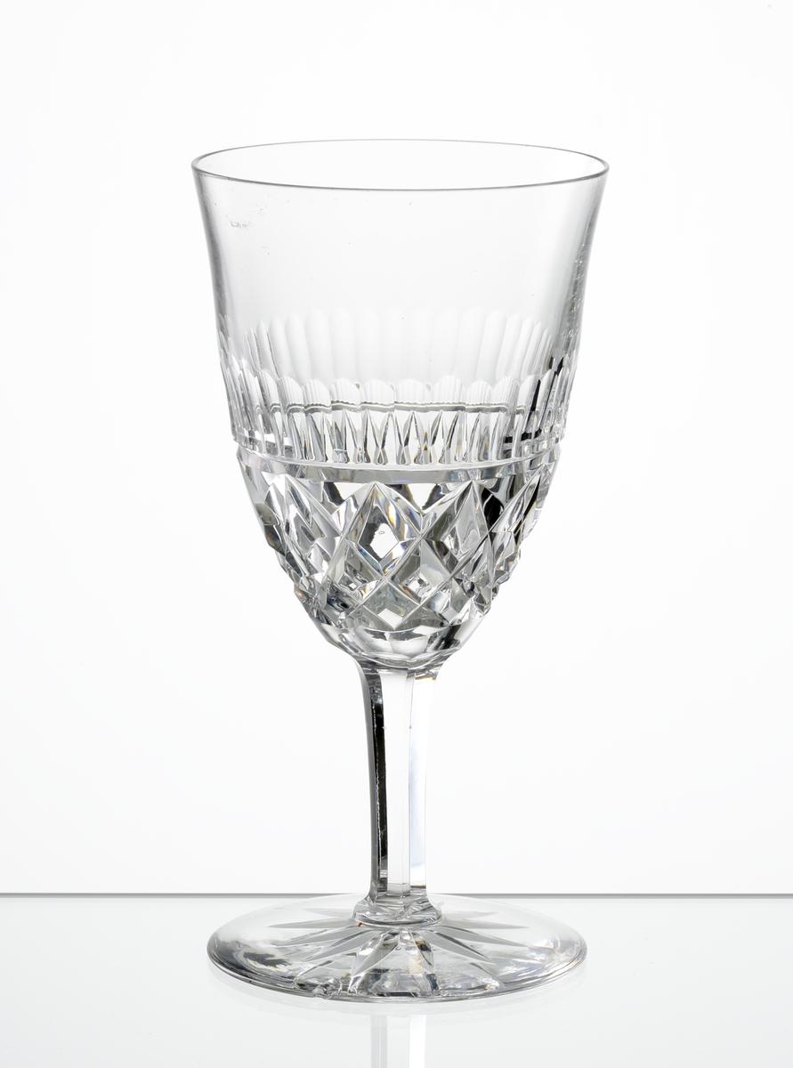 Vitvinsglas med lätt klockformad kupa, skärslipad nedre del med olivslipad bård. Fasettslipat ben. Fot med skärslipad stjärna i botten.