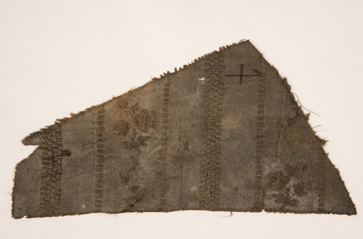 Testilfragment av silke. Randigt med blomkvistar. trolgen 1780-tal.