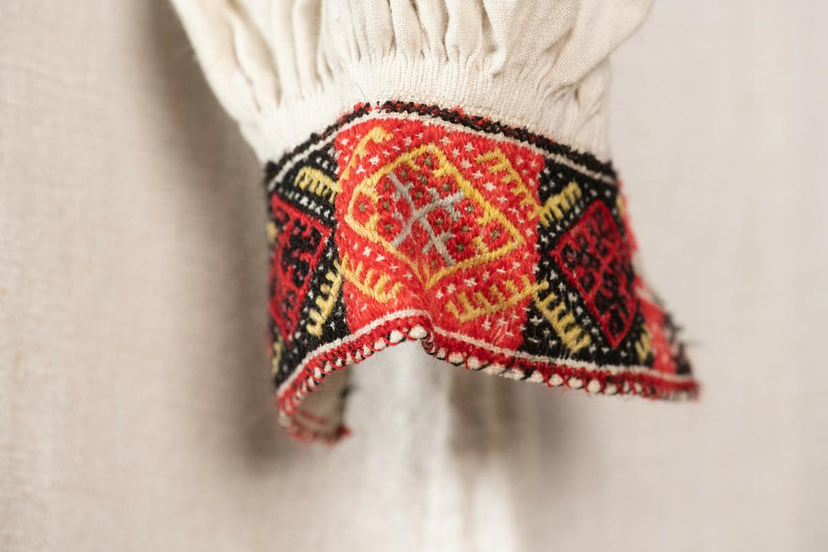Kvinneserk. Overdel av ubleket, hjemmevevd lin og underdel av strie. Rett usydde ermer med ermekiler og innfelte skulderstykker. Splitt foran og tette legg ved hals og håndledd. Både hals- og ermlinningene er smøygbrodert i ullgarn, med mønster av romber og kors. Ermlinningene er klippet i ett med ermet. Halssplitten har grunnsøm og under denne en A brodert i rødt garn. Serken er håndsydd.
