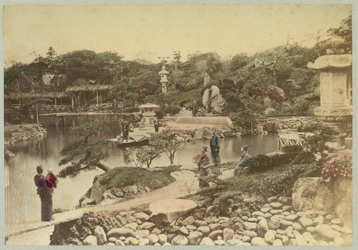 Bilden visar en Daichini-do trädgården i staden Nikko i Japan. I trädgården syns ett flertal japaner i traditionella dräkter.