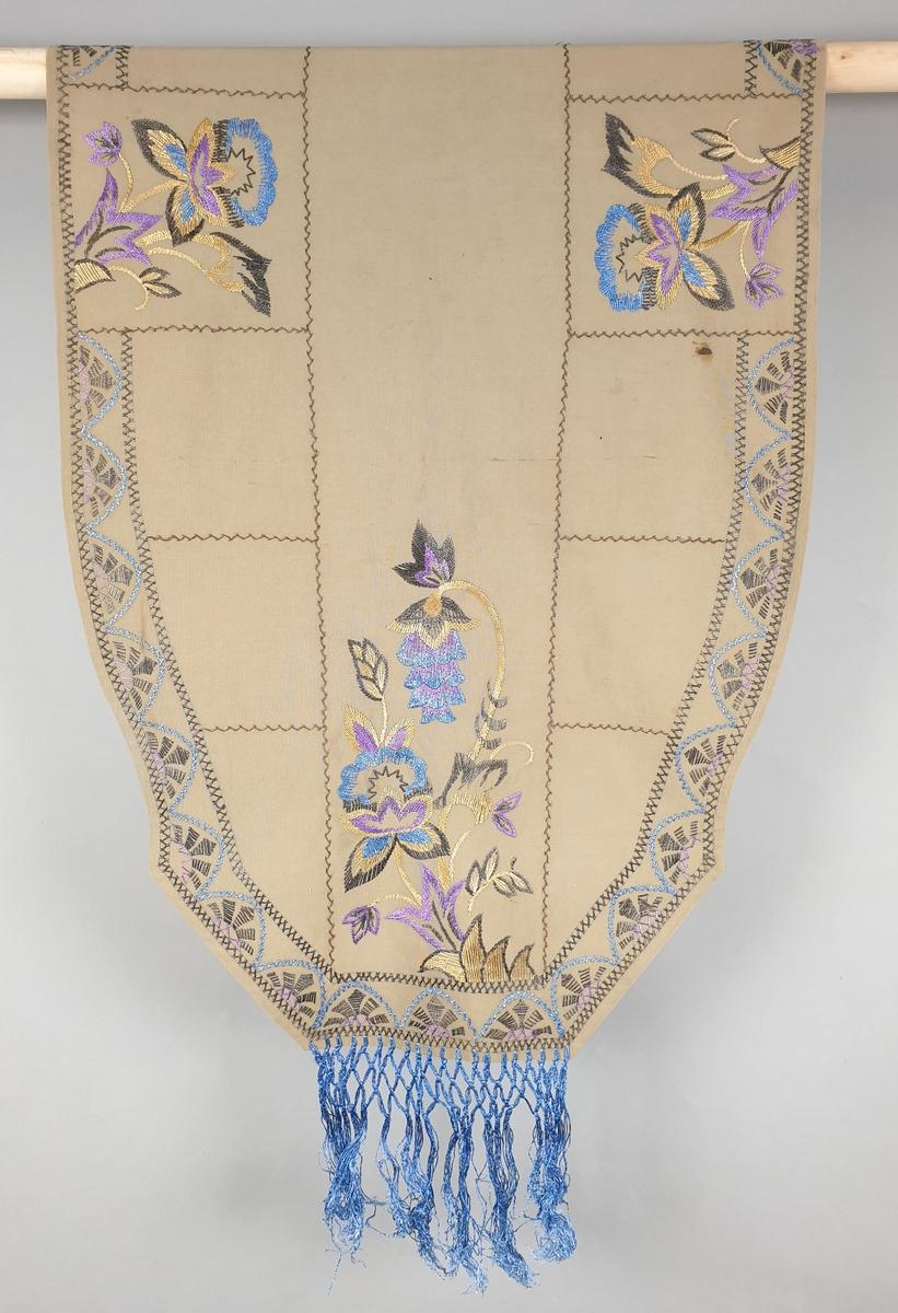 Tre broderte pynteduker, en stor med blå frynser på kortendene, og to mindre. Blomsterbroderi i blått, fiolett og mørkebrunt på lys brun bunn.