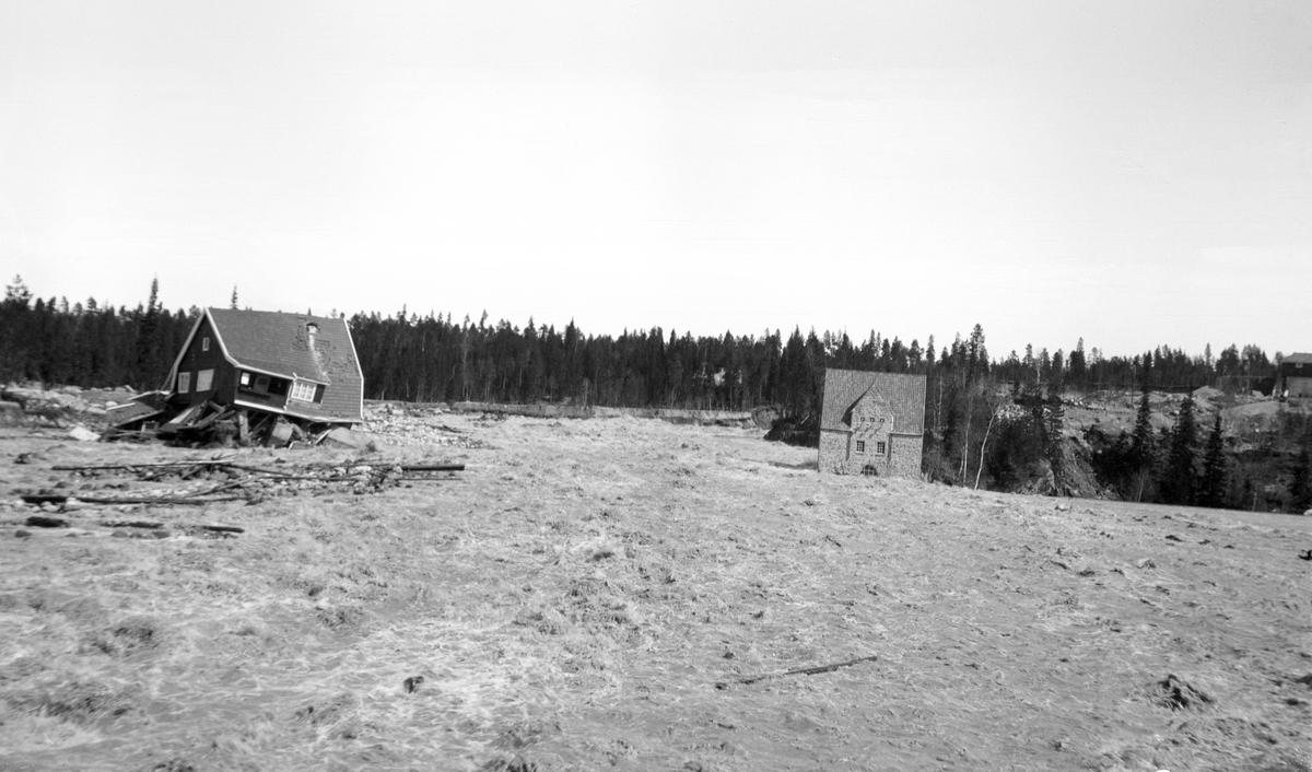 Fra den såkalte Osfallskatastrofen i 1916.  Bildet er tatt nedenfor Osfallet kraftstasjon i elva Søndre Osa i Åmot i Hedmark 11. mai 1915, dagen etter at den nordre damarmen ved det ovenforliggende kraftverksreservoaret brast.  Konsekvensen av dette dambruddet ble at elva skylte med seg trær, sand, grus og stein og dannet seg et nytt løp nord for det opprinnelige.  Her, i den sørvendte elveskråningen, lå maskinistboligen kraftutbyggerne hadde fått bygd.  Den to etasjes trevillaen greide ikke å motstå vannmassene og all den grusen og steinen de førte med seg.  Det verste var at både maskinisten og mora hans oppholdt seg da den ble tatt av den kraftige vannstrømmen.  Maskinisten forstod at de måtte redde seg ut, men da han åpnet døra, ble bygningen fylt av vann og grus, slik at førsteetasjen kollapset.  Mora ble klemt fast under en bjelke.  To dyktige og dristige fløtere tok seg ut til bygningen i båt, men mens de hogg den bjelken som gjorde at den eldre kvinna satt fast, døde hun.  Maskinisten greide de imidlertid å redde over på trygg grunn på sørsida av elva.  Dambruddet forårsaket enorme materielle skader på et nesten nytt kraftanlegg, noe som innebar store økonomiske tap for utbyggerne, Åmot kommune.  Mer informasjon om kraftutbygginga og det påfølgende dambruddet ved Osfallet finnes under fanen «Opplysninger».