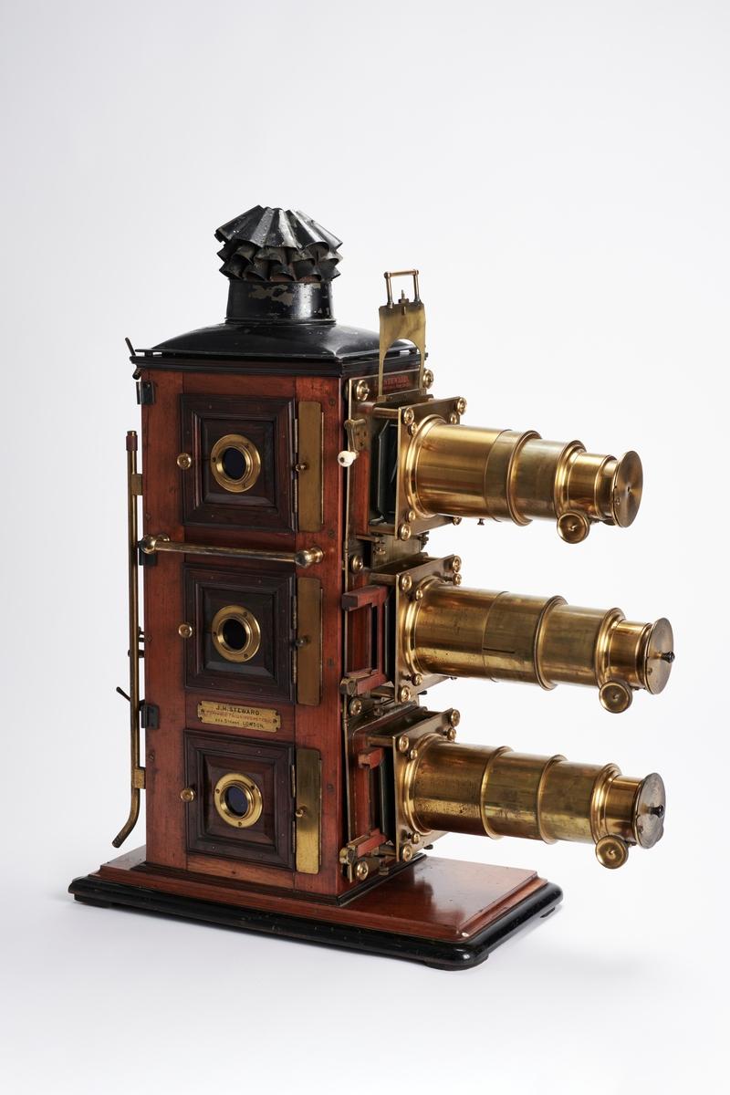 """En Triunial Magic Lantern er et projeksjonsapparat, som skiller seg fra en vanlig Magic Lantern fordi den har tre objektiv og ikke bare ett. De tre objektivene gjør det mulig å produsere mer """"levende"""" bilder ved å projisere bildene oppå hverandre."""