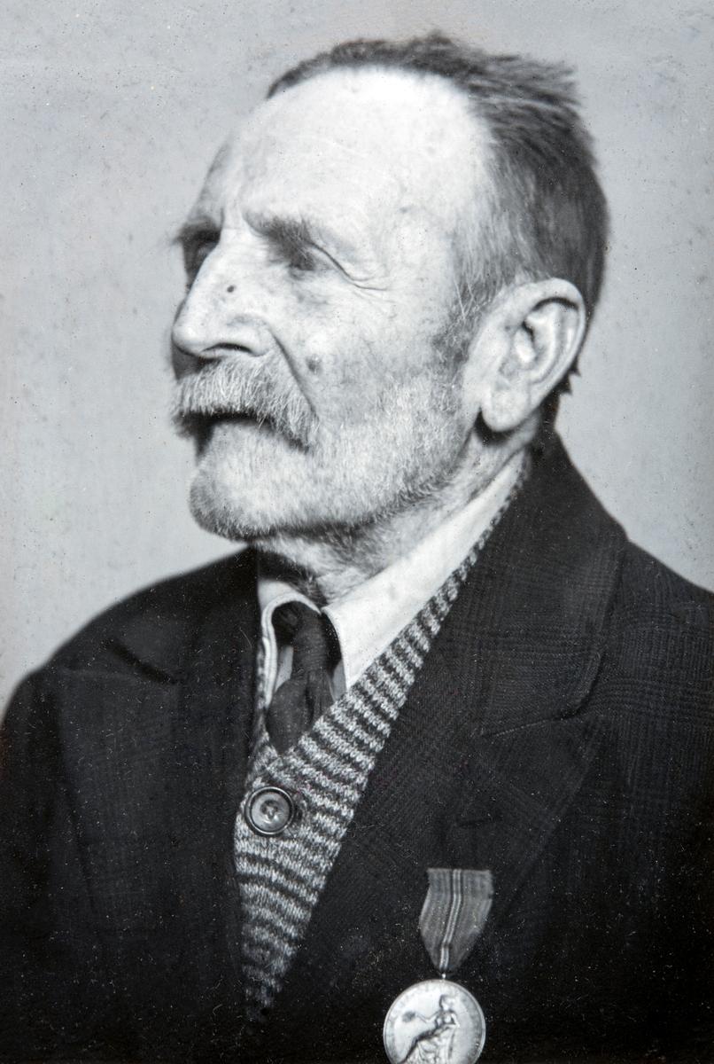 Portrett av Husmann Nils Olsen Hagen (29.01.1863-24.10.1955), Han var husmann på Hverven Gård i Ottestad, i rundt 60 år. På bilde har han medaljen for lang og tro tjeneste i fra Norges vel. Bildet er tatt i forbindelse med hans 90-års dag i 1953.