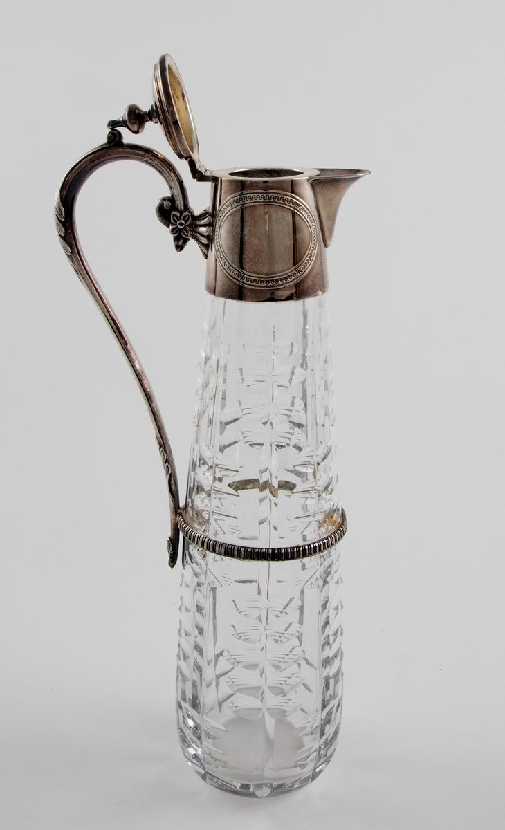 """Høyreist kanne i klart glass med påmontert hank og lokk i sølvplett. Konisk korpus som er dekorert med sliping, i form av vertikale linjer som flankeres av parvis olivensliping. Svungen hank i sølvplett med blomsterdekor. Plettmonteringen på kannens øvre del har graverte ovaler, samt innpunslet inskripsjon: """"Erindring / af / 23.9.82"""". Mykt buet nebb samt henglset lokk med balusterformet lokknapp."""