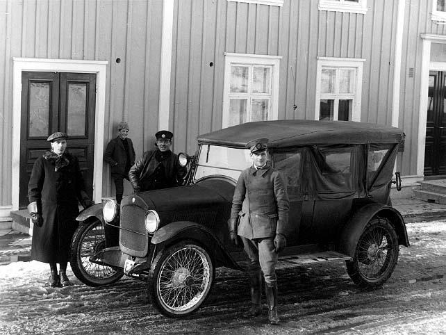 """""""Eklund med sin hyrbil"""". En bil står parkerad utanför Hotell Brahe i Gränna. Det är en Hupmobil med registreringsnr F327. Hitom bilen står en man i chaufförsuniform, möjligen Eklund. Till vänster vid bilens front står en man i keps och rock med pälskrage, det är chaufför Harry Håkansson. Bakom bilen står en okänd man i keps, skinnjacka och troligen uniform - Harry Siebke? Mot husväggen står en pojk med pälsmössa och ler mot fotografen, möjligen David Ebbesson. Det är snöslask på gatan."""