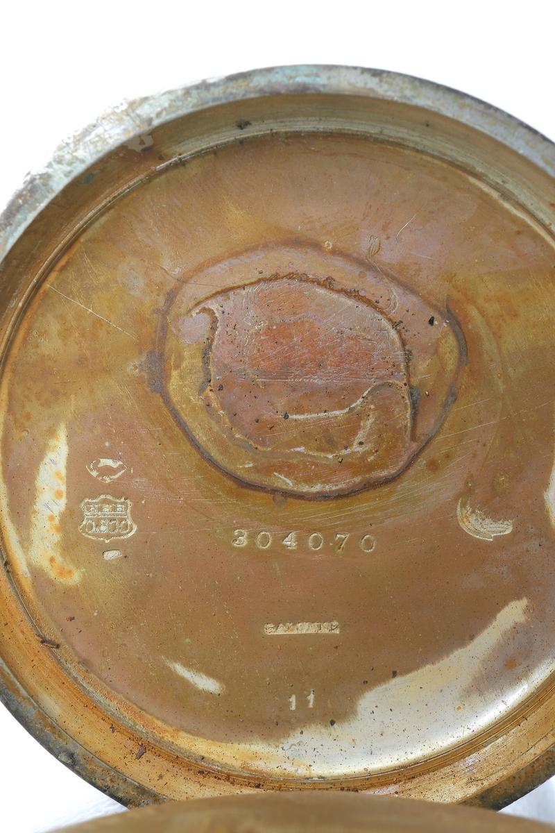 """Fickur i silver som dras upp med krona. Runt kronan finns en bygel för att fästa en klockkedja. Den främre boetten har ett glas monterat framför urtavlan som består av vit emalj. Visarna är utsirade i guldfärg, och nedtill en mindre urtavla för sekundvisning. Bakboetten har ett mönstrat motiv liknande det svenska riksvapnet med två lejon på vardera sidan om en sköld krönt med en krona. Boettens ytterkanter är guldförgyllda. Ytterboettens insida har en stämpel liknande en halvmåne och en kungakrona, samt en större och en mindre som liknar en orre. Vidare finns numret """"304070"""" och """"0.800"""" inramat. Även """"GALONNE"""" finns stämpalt och siffran """"11"""". Innerboettens utsida har ett graverat mönster bestående av ett liggande lejon med en sköld med de tre svenska kronorna vid sidan om. Vidare finns texten """"1/2 CHRONOMETRE REMONTOIR SPIRAL BREGUET"""" och """"CHATON OR 19 RUBIS"""" samt """"BALANCIER COMPENSSÉ"""". Innerboettens insida har numret """"304070"""" och stämpeln liknande halvmåne och krona inslaget, samt """"0.800"""" inramat. Verket utan stämplar.  Klockans skyddsboett i två delar, består av en överdel med ett fönster i celluloid, och en underdel att lägga uret i. Baksidan märkt med """"23 1/2"""" och """"Herkules D.R.G.M. 160717"""". Dosan troligen i nickel."""