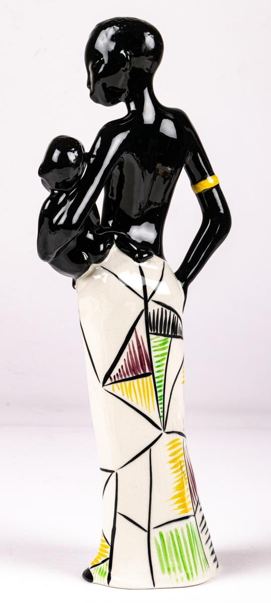 Figurin föreställande svart kvinna med ett barn på höften, flintgods, handmålad, glaserad. Djuptryck på undersida C.15 vilket står för formgivare Dorothy Clough, samt stämpeltryck med Gefles logga med tre rundugnar.