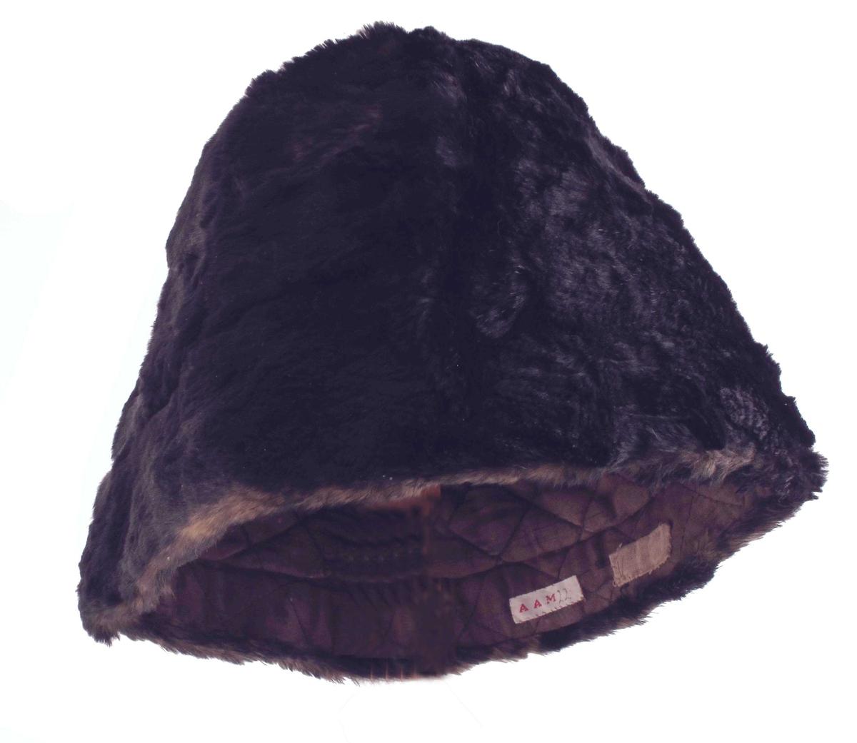 Skinnlue, sort bisam, brunlig vattert for. Tilstand okt, 1959: Slitt i kantene, foret temmelig  skittent og avfarget.  Innvendig ved kanten påsydd gulhvit grov Lerret-  slapp, uten synlig på skrift.