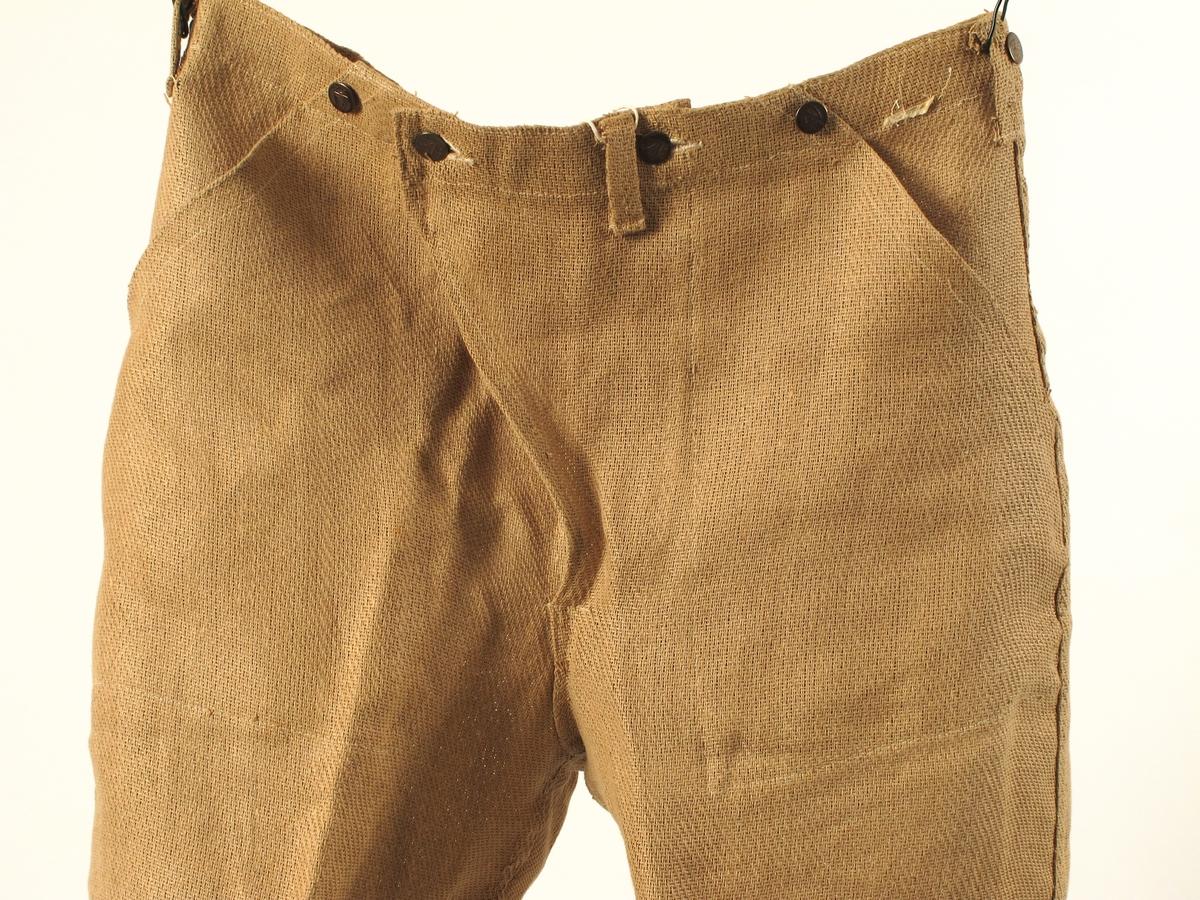 """a) Dressjakke. b) Dressbukse. Ved innkomst lå dressen i en brun pappeske fra Elms herrekvipering. Om dressen opprinnelig er levert kunden i denne esken er høyst usikkert. Opplysningen om forhandler er derfor en høyst usikker opplysning. Pappesken er registrert som nr. AAM.25356. Krigsmodell, krisevare, laget av papir. """"Tekstil"""", vevd av tvunnede papirstrimler. Er tilnærmet ubrukt."""