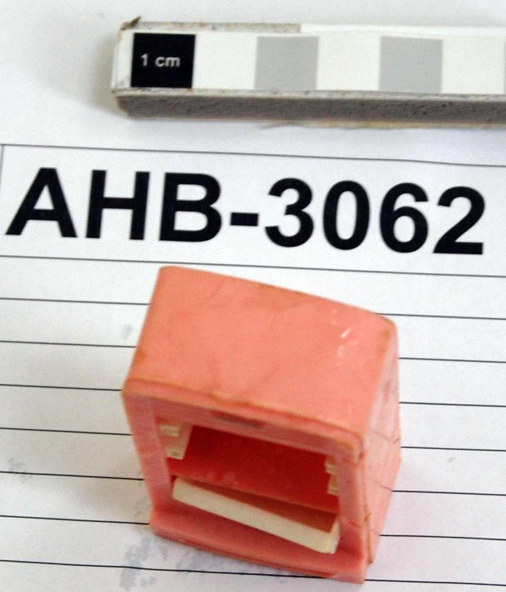 Dukkekjøleskap i rosa plast med hvit innredning. Originalt 2 hyller og grønnsakskuff. Døra og en hylle mangler