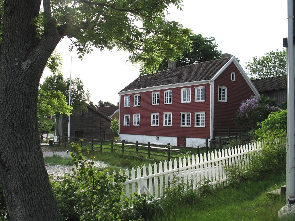 Merdøgaard, gårdstun sett fra V, sjøbod t.v. våningshus, fjøs bak t.h.  Tunntreet, lønn, synlig over våningshuset. I forgrunnen asketre og stakittgjerde.