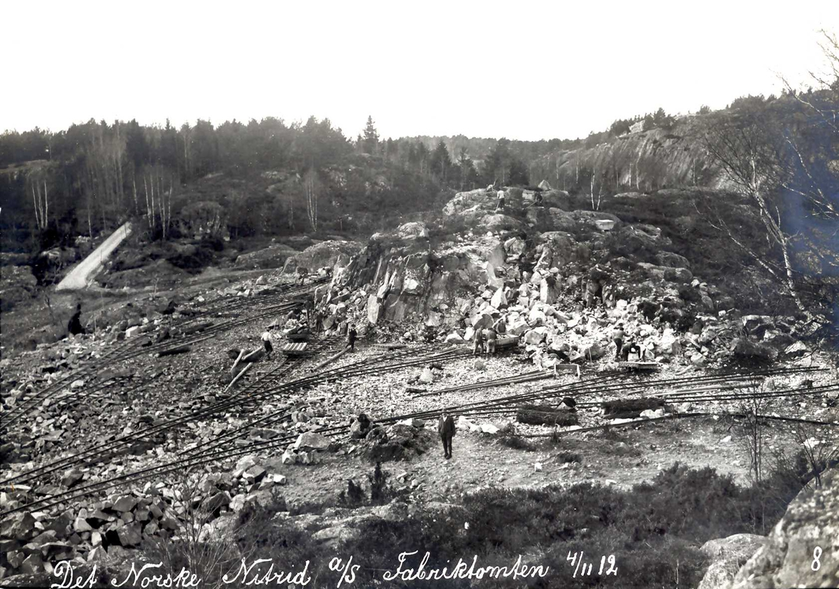 """""""04/11-1912"""" Nitriden. Utsprengning og planering av fabrikktomten. Skinneganger for traller for utkjøring av steinmasser. Forholdsvis store fjellpartier å gi seg i kast med. På høyden til høyre bygde man vannbasseng for trykkvann til bedriftene, Smelteverket og Nitriden. Til venstre vei."""