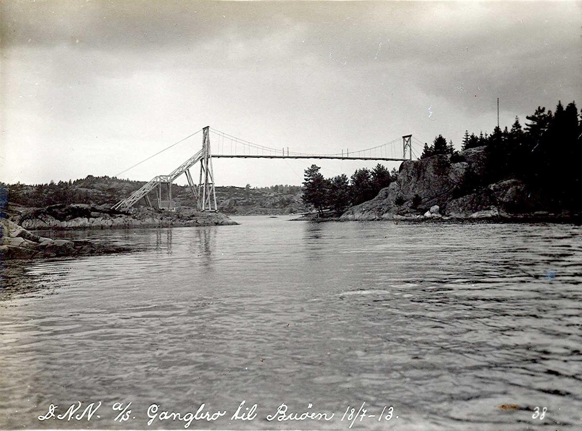 """""""18/07-1913"""" Nitriden. Gangbru fra Langnes (Pinnen) til Buøy. Kun tillatt adgang for dem som bodde på Buøy. Brua var så høy at marinens båter kunne passere under. Trekonstruksjon."""