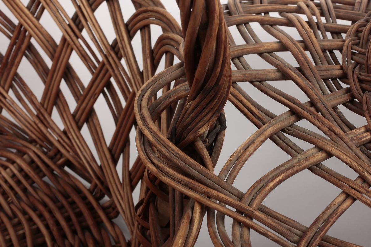 Korg m/tettflettet bunn ag åpnere mønster i sidene, sokkel. Håndtaket laget av peddik tvunnet gjennom kløvet kvist, går gjennom ytterkanten av lokket og holder dette. Lokket er svakt buet med en rett oppstående kant rundt et tettere flettet toppstykke.