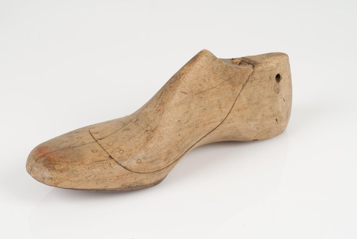 En tremodell i to deler; lest og opplest/overlest (kile). Høyrefot i skostørrelse 42, med 7 cm i vidde. Halv såle av skinn/lær.