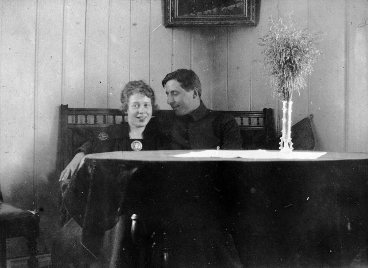 To unge mennsesker som sitter bak et bord.