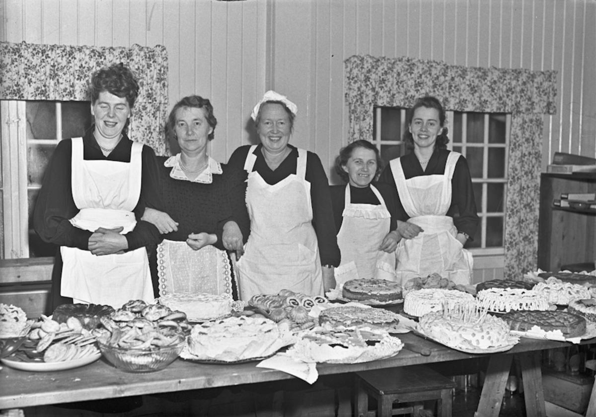 Kvinner ved et kakebord.