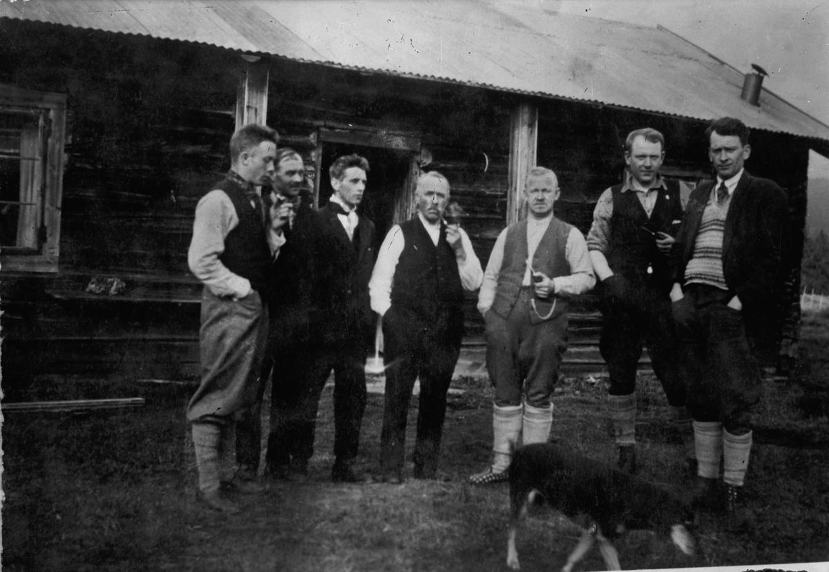 7 menn utenfor et tømmerhus.