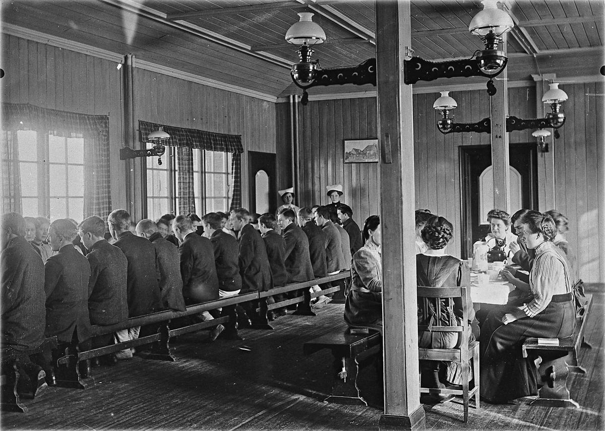 """Eidsvoll Folkehøyskole 22. juli 1914. Fra spisesalen. Bordene dekkes. Maleriet til venstre på veggen er av Lars Jorde: """"Sommernatten"""". Maleriet til høyre av Olaus Arvesen er av samme maler. Navn som sto bak på bildet: Karen, Karin, Marie og Boline."""