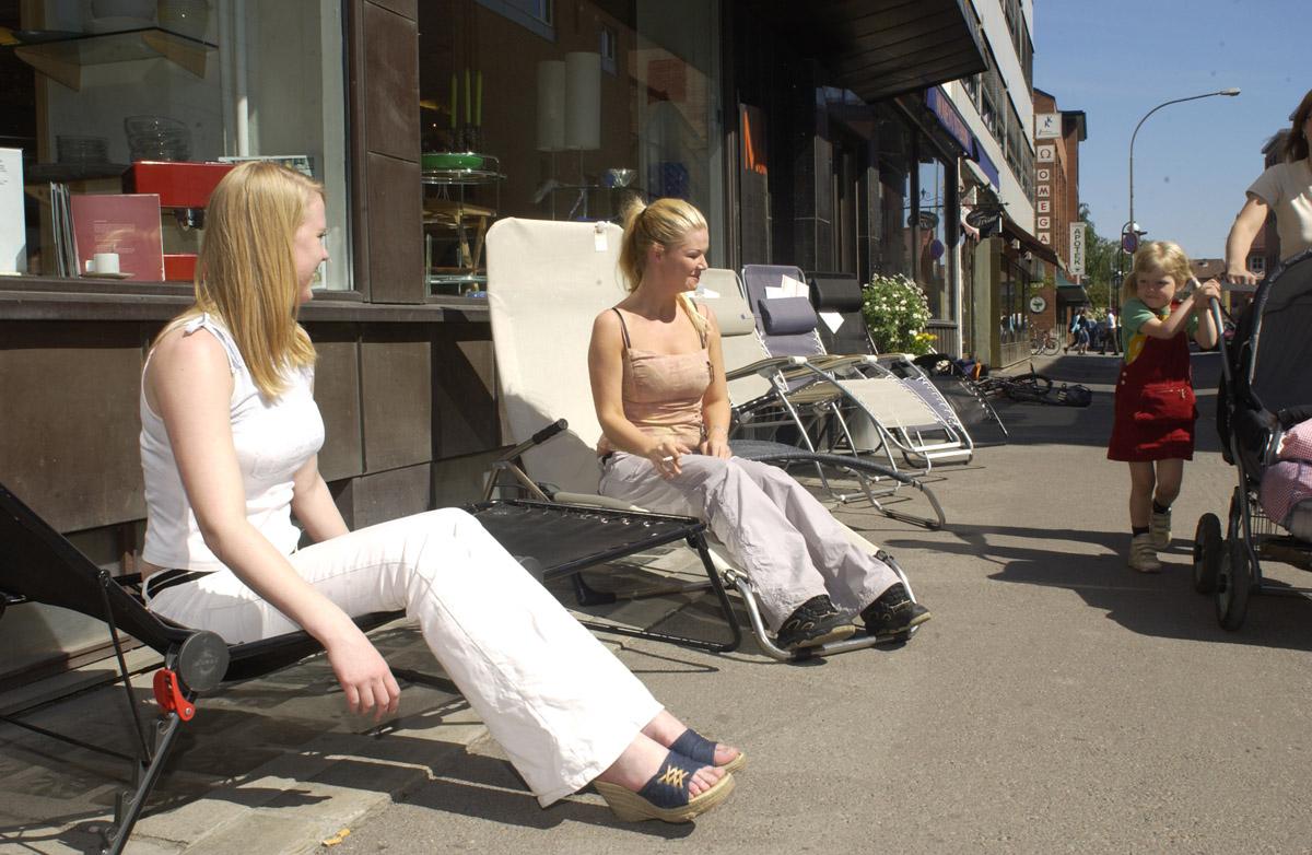 Første dagen med ny røykelov 2004. To røykende jenter på solsenger foran Willys Conditori. Røykepause.