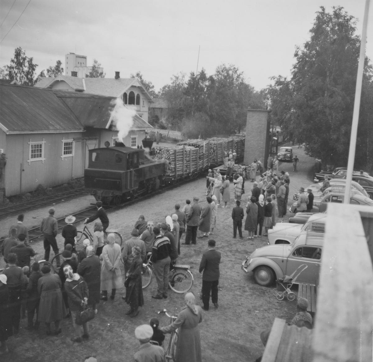Siste ordinære tog fra Sørumsand til Skulerud kjører inn på Bjørkelangen stasjon. Lokalbefolkningen har møtt frem på stasjonen. Fotografen står i 2. etasje i stasjonsbygningen.