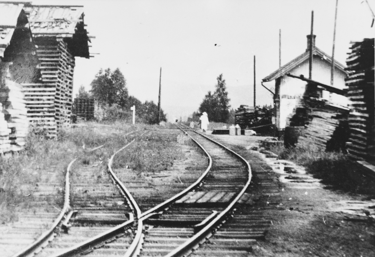 Ved- og plankelagre som venter på transport, trolig under krisen i 1918. Det pågår oppsetting av stolper for elektrisk belysning. Stasjonen har fremdeles utvendig parafinbelysning.