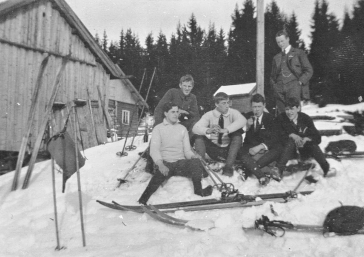 Seks unge på skitur. Pause ved hytte.