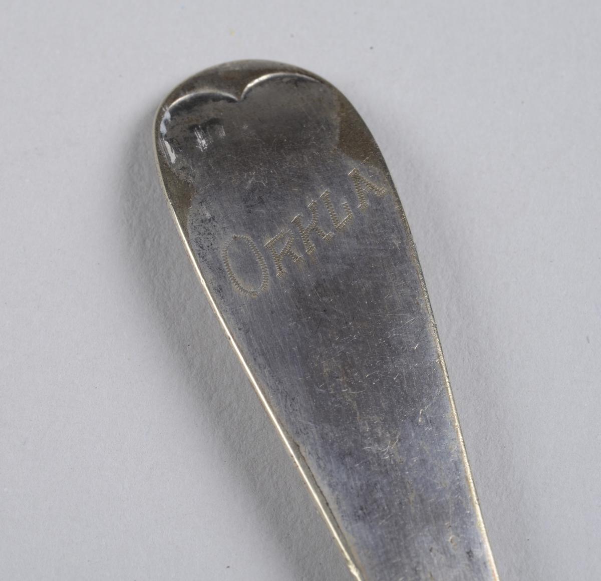 Skje med enkel dekor i form av en midtstilt opphøyning på enden av skaftet.