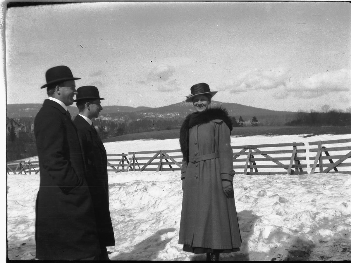 To menn med bowlerhatt og en kvinne med pels foran et jorde.