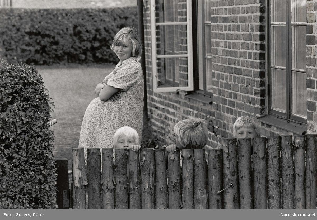 Gravid kvinna med stor mage tittar på tre barn vid staket.