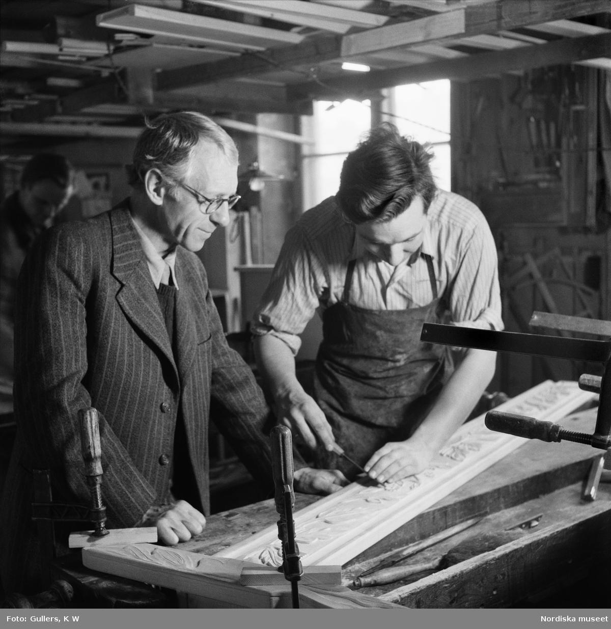 Professor Carl Malmsten, möbelformgivare och inredningsarkitekt, i snickeriverkstad tillsammans med snickare.