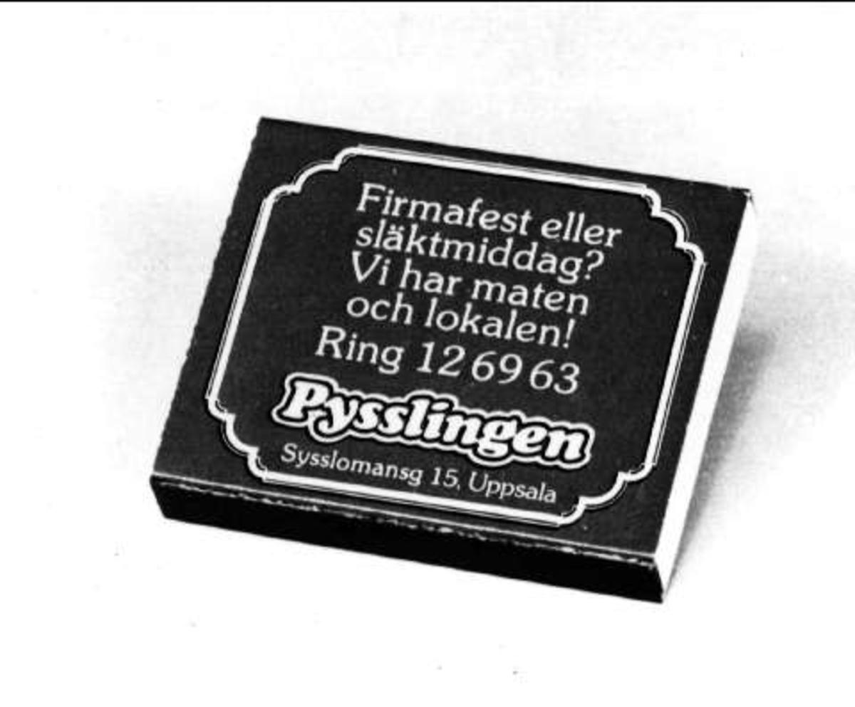 Blå och gul tändsticksask av papp med reklamtext för restaurang Pysslingen, Sysslomansgatan 15, Uppsala. Vitt svavel på tändstickorna.