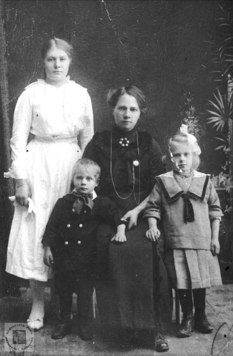Portrett av ukjent mor med konfirmant og småbarn.