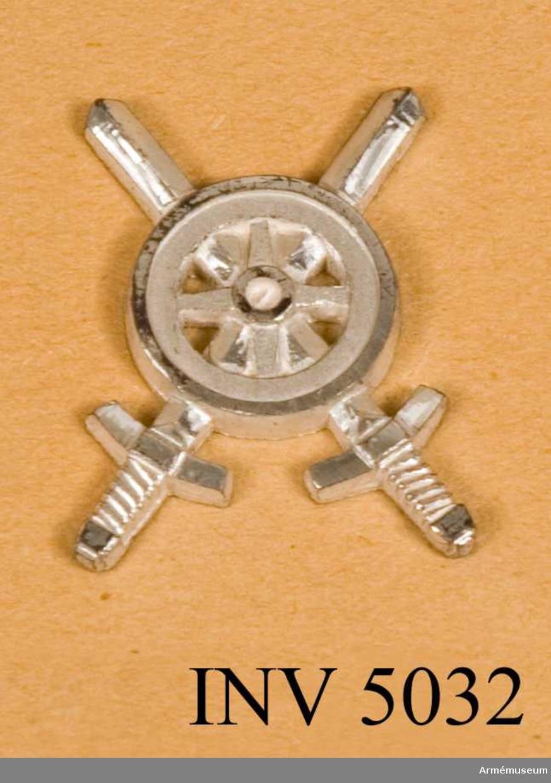 Tillverkat av metall. I likhet med emblemen till  trängtruppernas äldre uniformer är det här utfört i silverfärg. Samma motiv som i 1939 års modell, ett kärrhjul på två korslagda svärd, men något annorlunda utformat.