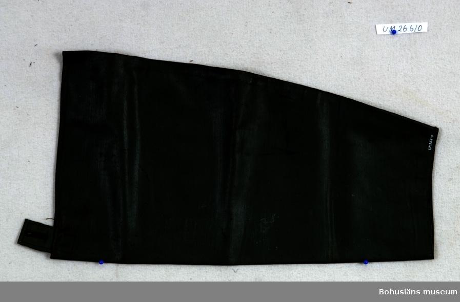 Grön avlång ärm. Upptill är det en grön stropp med ett knapphål.  Att dra utanpå skjorta som skydd för väta. Denna typ av mudd såldes av Torvald Strannes skeppshandel på Smögen.  Övrig historik; se UM026422