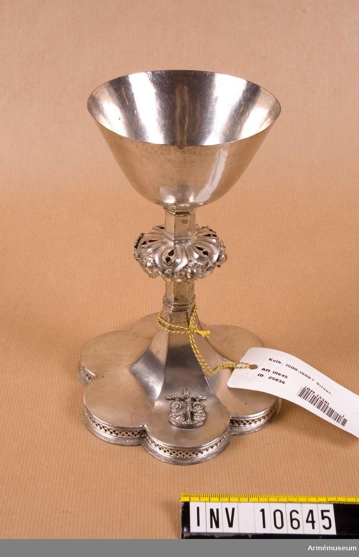 Grupp B II. Av silver, kring halsen en pålödd, genombruten ring med stiliserade bladornament, foten försedd med genombruten ornering och på densamma en korsfästelsescen.