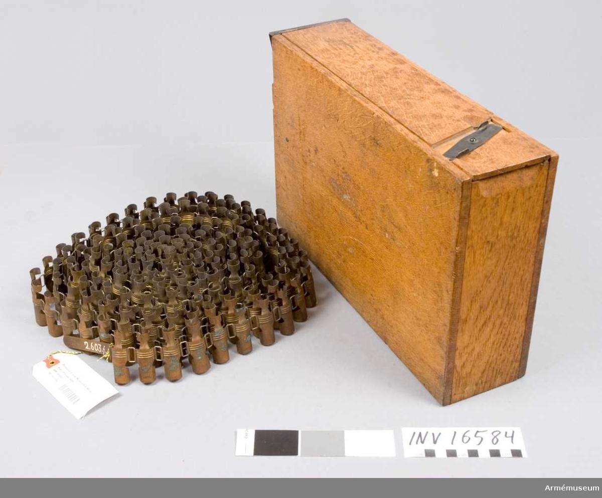 1 bandlåda av ek med järnbeslag, 370x245 mm, vikt: 1800 gr. 1 länkband av mässing, l: 5130 mm. För 200 skott.
