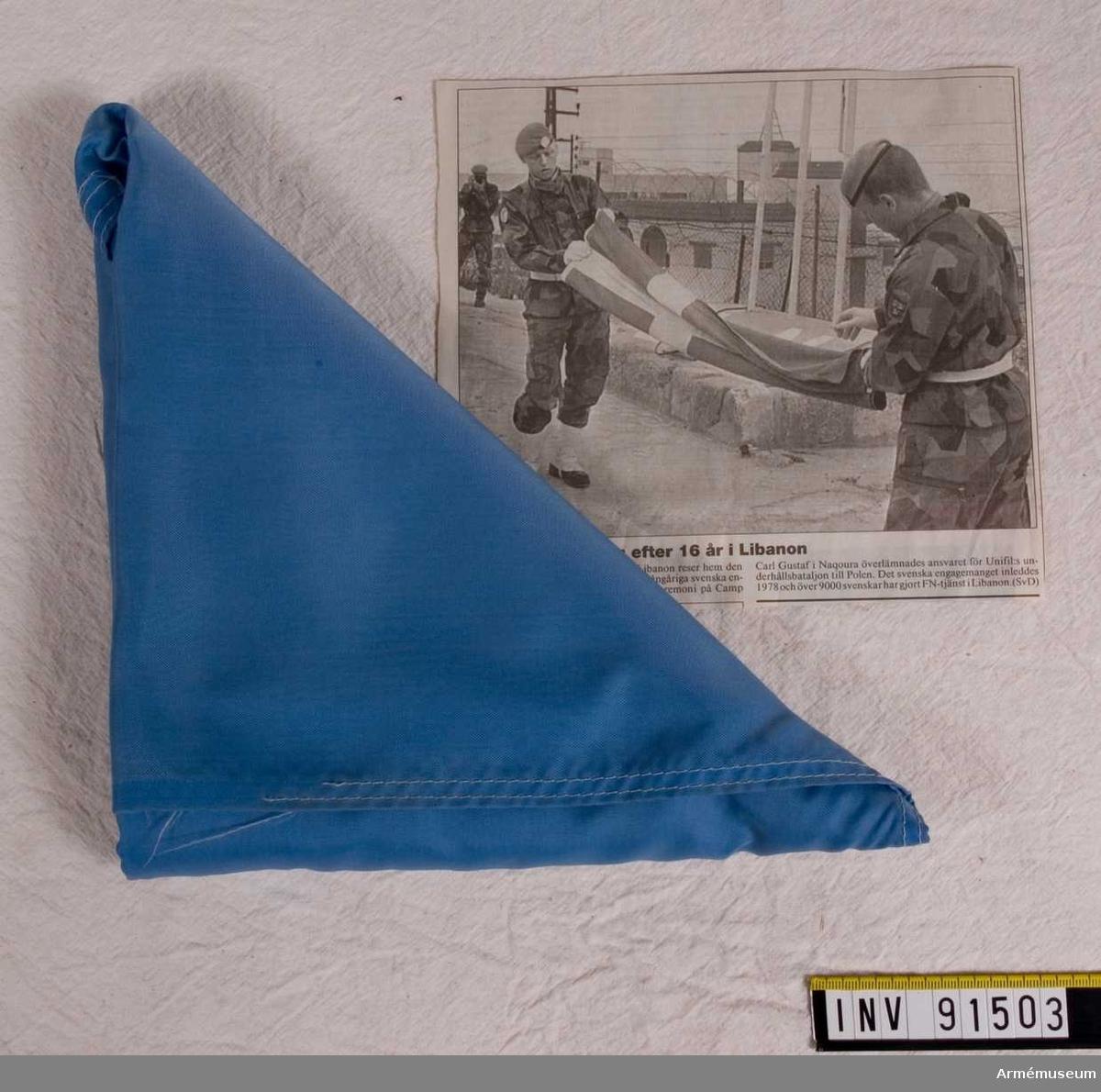 Hopvikt svensk flagga som överlämnades till gmj. Rönnberg vid en cermoni 94-07-04, samt tidningsurklipp om detta.