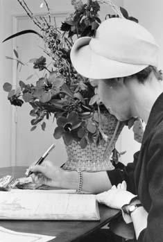 Uppvaktning å postsparbankschefens Sven Lönnqvist tjänsterum.  Foto 10/3 1959.  Fru Vanhala, Finland, skriver sitt namn i gästboken.