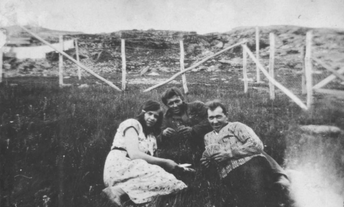 Tre personer ligger i gresset. Sted og personer er ukjent, men fotografiet kan være tatt i Kvalsund kommune.