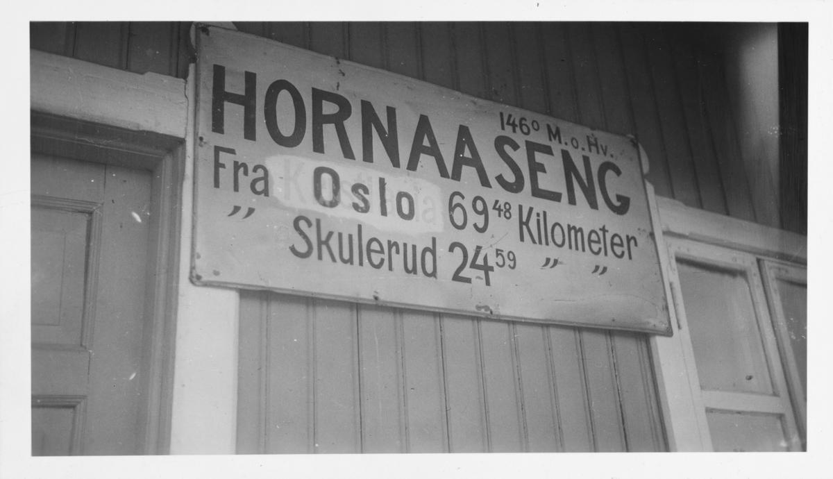 Stasjonsskiltet på Hornåseng stasjon fotografert i juni 1959. Stasjonsnavnet er ikke endret fra Hornaaseng. .