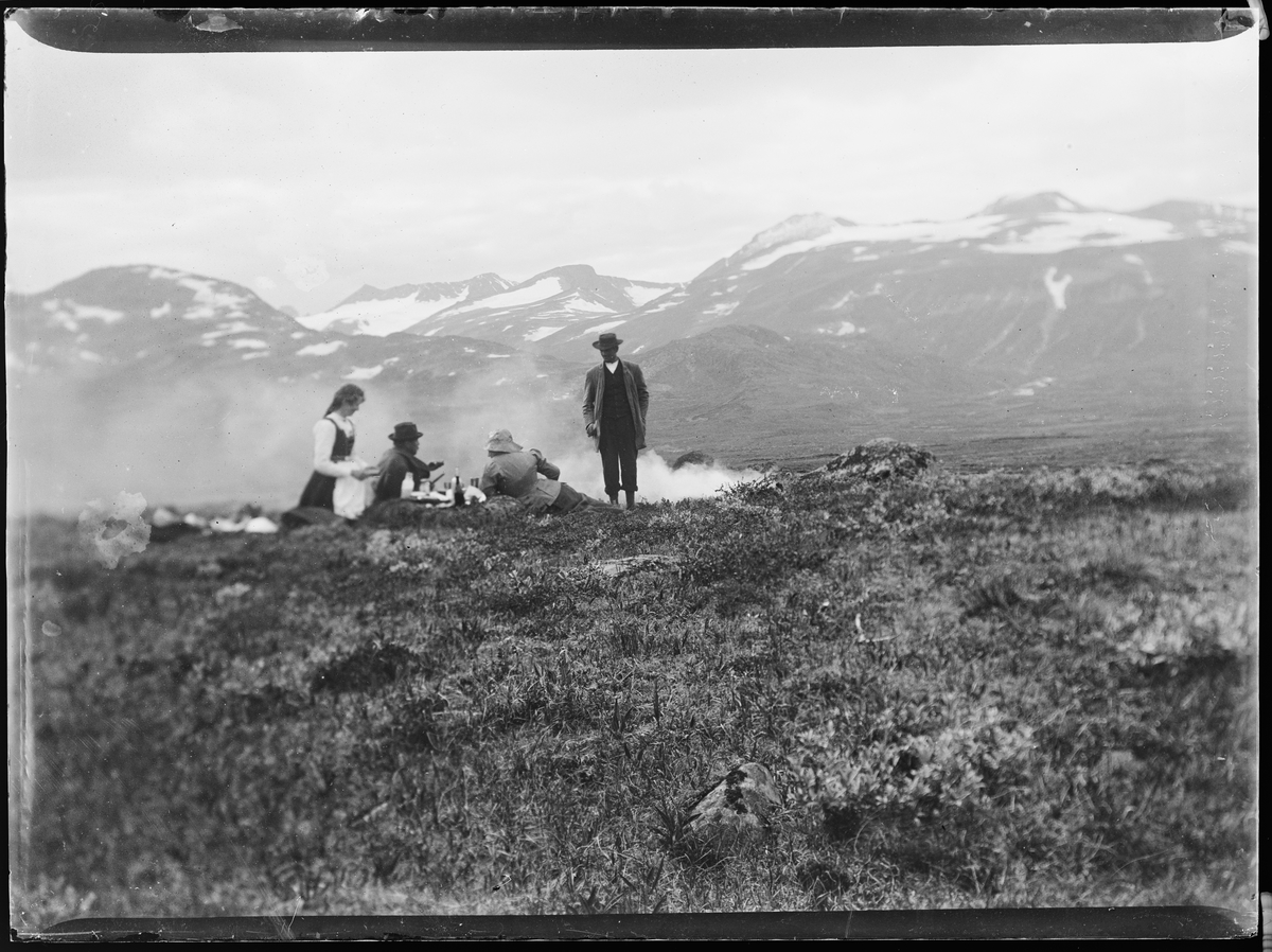 """""""Heimdalen 1906"""" (inskr eske). Fra Sjølisæter ved Atnsjøen. Fjellandskap. Snødekte fjell i bakgrunnen. Tre personer ligger i lyngen, en mann står. Det ser ut til at de har tent et bål. Alle er vendt fra kameraet."""
