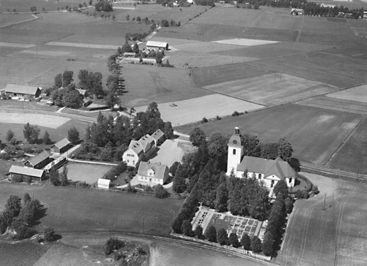 Flygfoto över Rinkaby kyrka, bostadshus, skola. Bilden tagen för vykort.