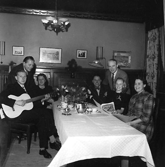 Rumsinteriör, sju personer vid bordet. Kafferep.