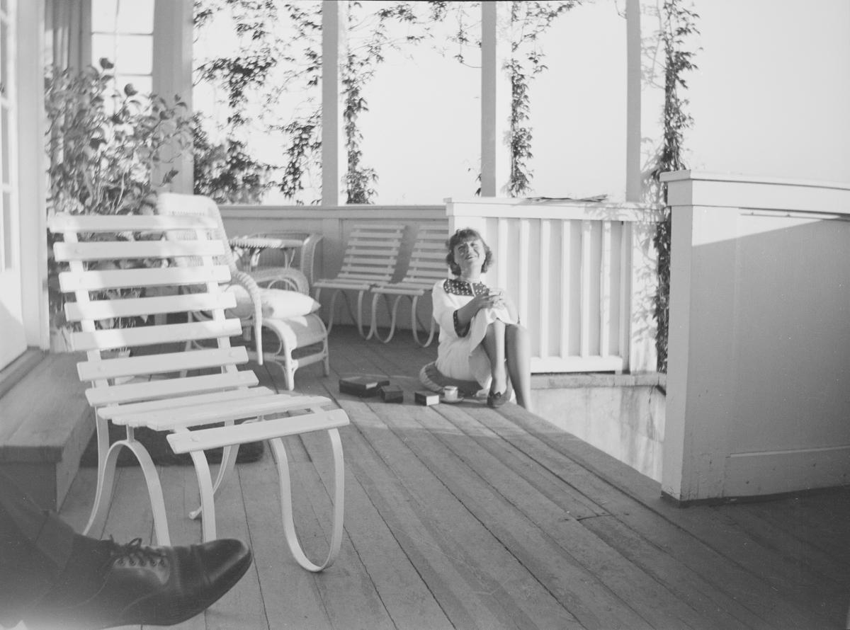 En kvinne sitter øverst på en verandatrapp med kaffe og sigarett. Ved siden av henne på gulvet står noen bokser. Verandaen er møblert med stoler og bord. Klatreplanter henger fra taket. En herrefot med sko sees i det ene hjørnet av bildet. Det er sommer på Linderud Gård.