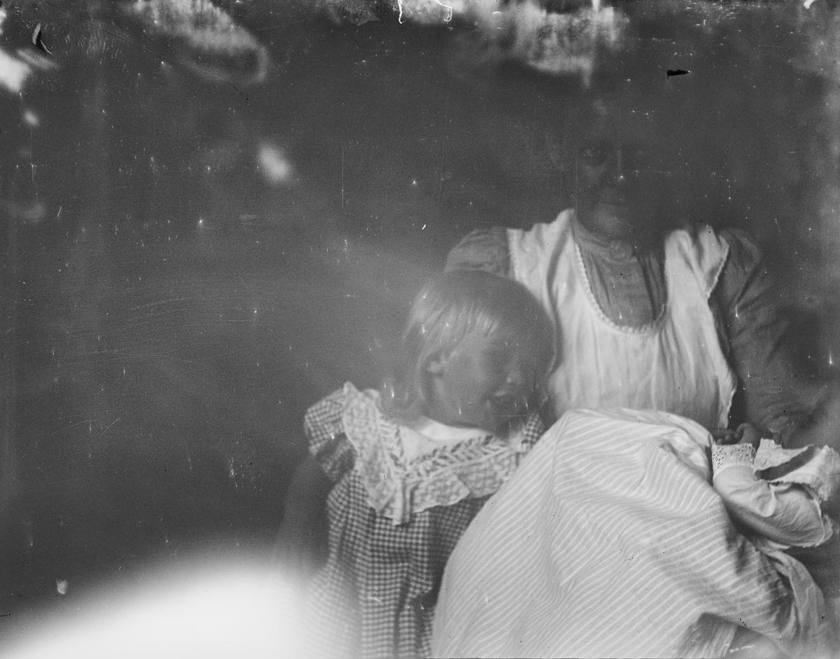 En sittende kvinne holder et barn tett inntil seg.