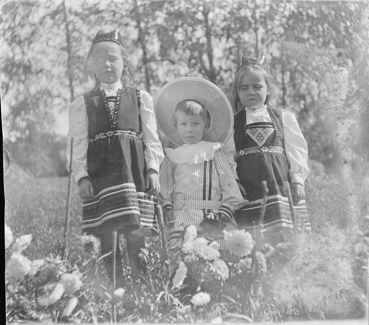 To jenter i hardangerbunad med perlet bringeduk og belte og en gutt står ved et blomsterbed fullt av georginer/dalia.