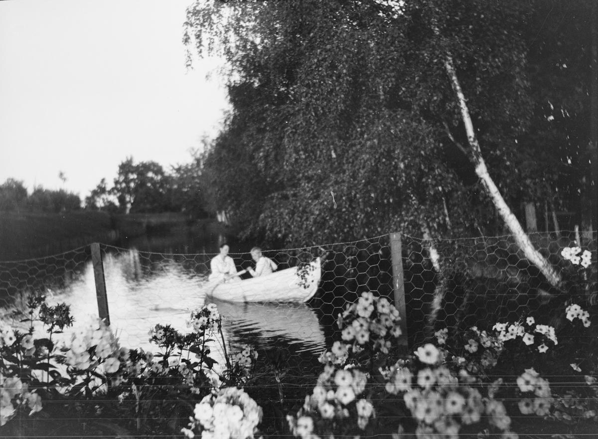 """En gutt er ute å ror på karpedammen også kjent som """"kanalen"""". Dammen ligger nederst i terrassehagen på Linderud Gård og går langs med """"Lindehallen"""". En kvinne sitter bak i båten."""