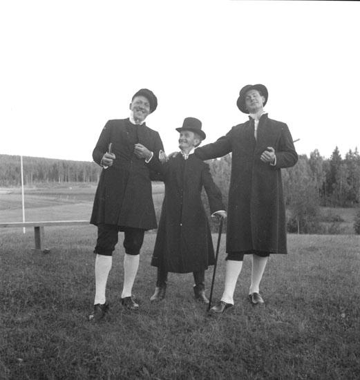 Festligheter vid Siggebohyttan den 30 juli 1937. Tre utklädda män spelar teater eller är uppklädda till dans.